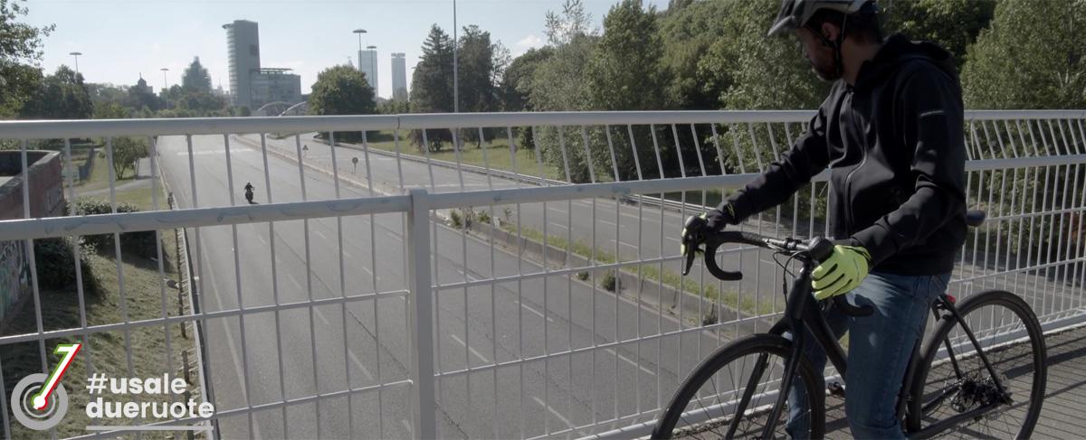 Ciclista osserva il passaggio di una moto da un cavalcavia