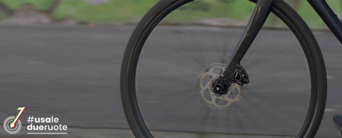 Il particolare di una ruota di bicicletta a spasso per la città