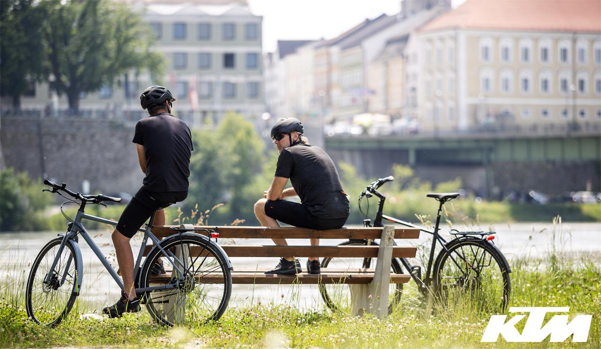 Due ciclisti si rilassano su una panchina con le loro bici urban KTM a fianco