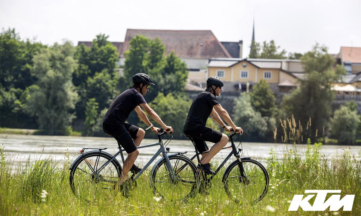 Due ciclisti pedalano in sella a biciclette da trekking urban KTM 2020