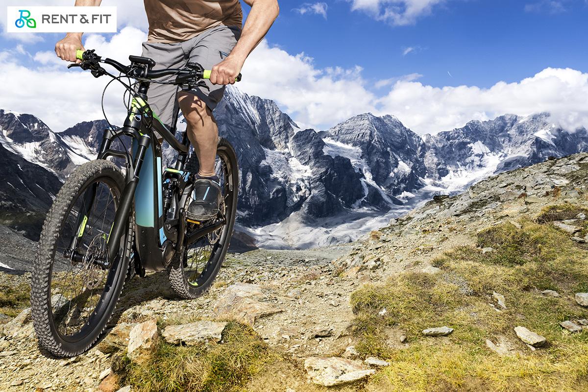 Uomo pedala su una Mountain bike noleggiata tramite il servizio online Rent & Fit