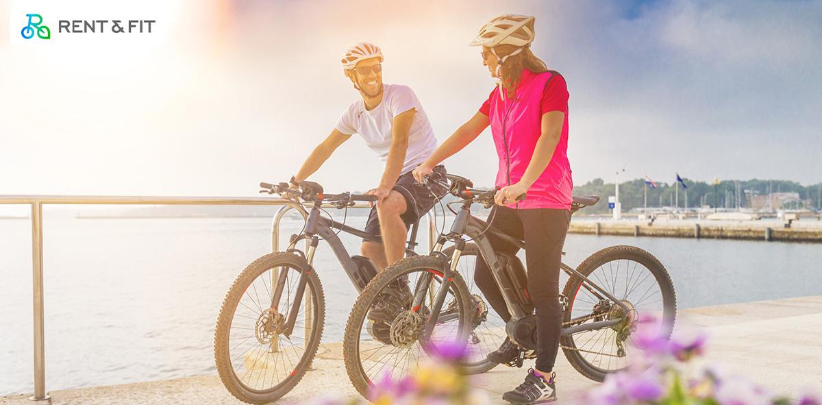 Una coppia pedala insieme su delle bici a noleggio di Rent & Fit