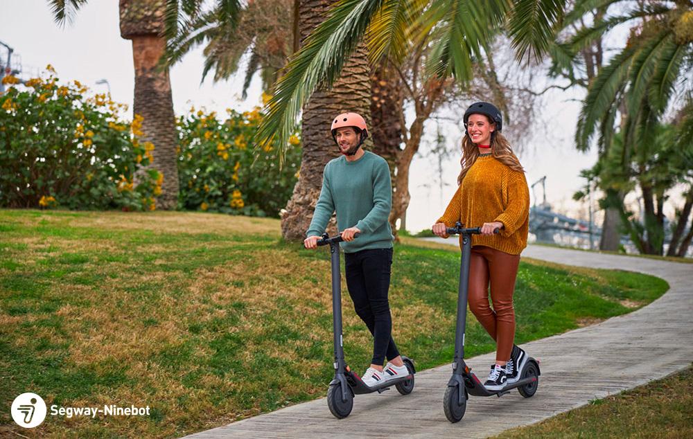 Una coppia felice si sposta su due monopattini elettrici Segway Ninebot E22E