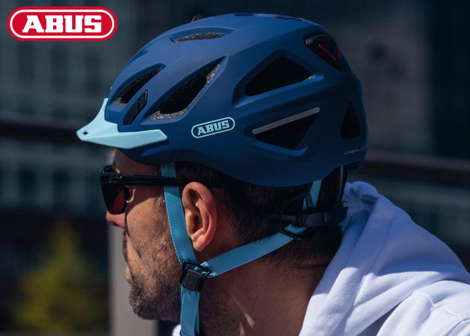 Un ragazzo indossa il casco ABUS Urban-I 3.0 in colorazione blu con visiera azzurra