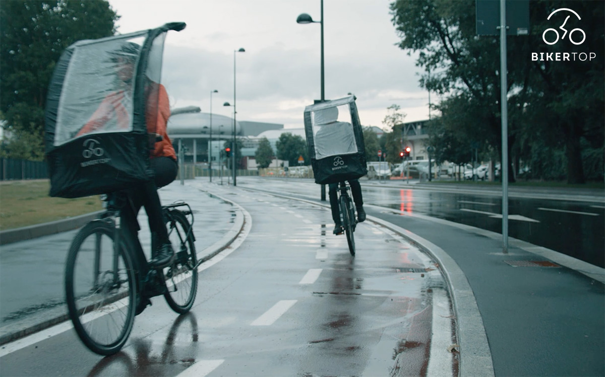 Due persone pedalano sotto la pioggia riparati dal parabrezza removibile Biker Top
