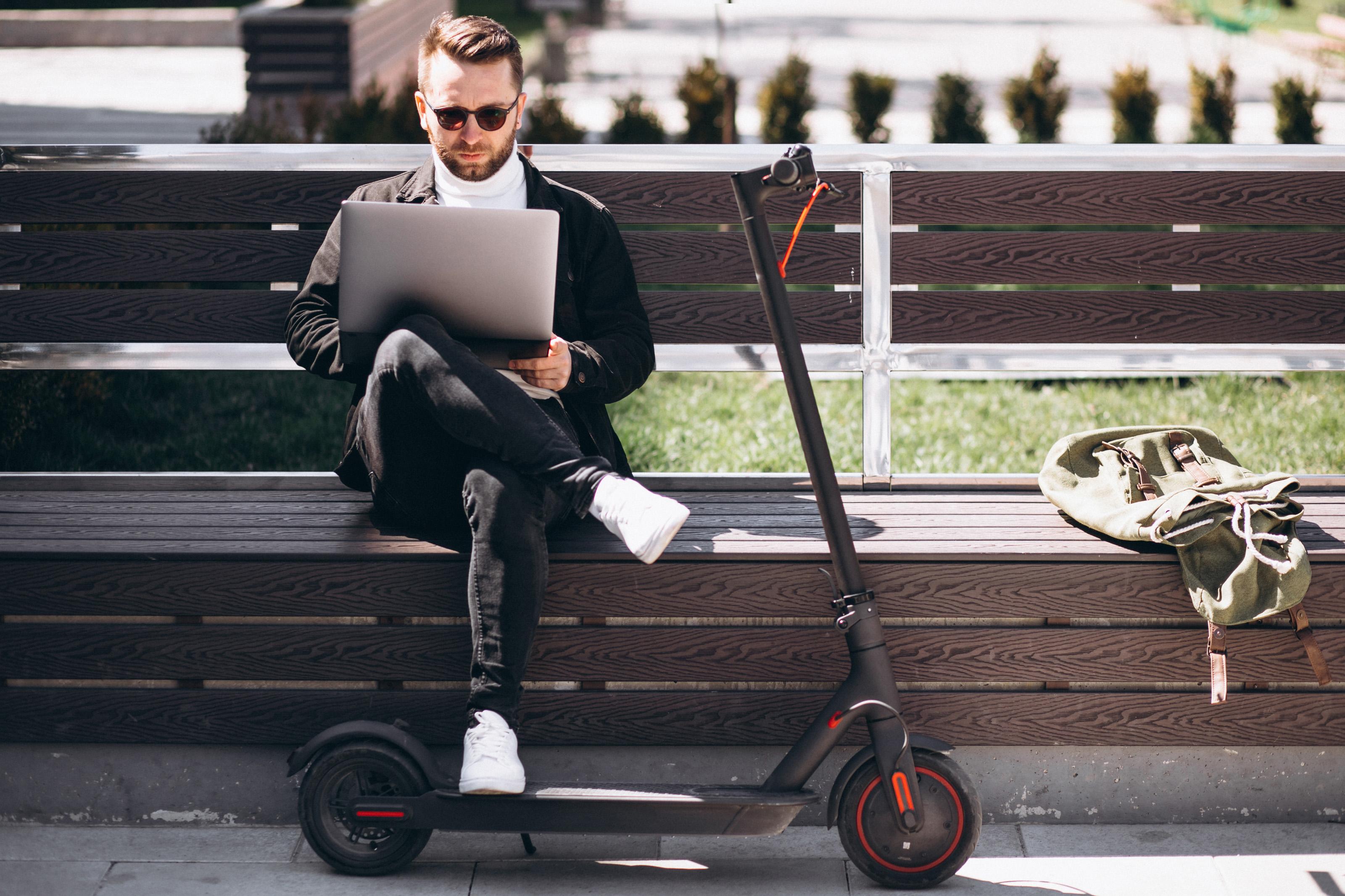 Un uomo richiede il bonus mobilità dal suo pc dopo aver acquistato un monopattino elettrico