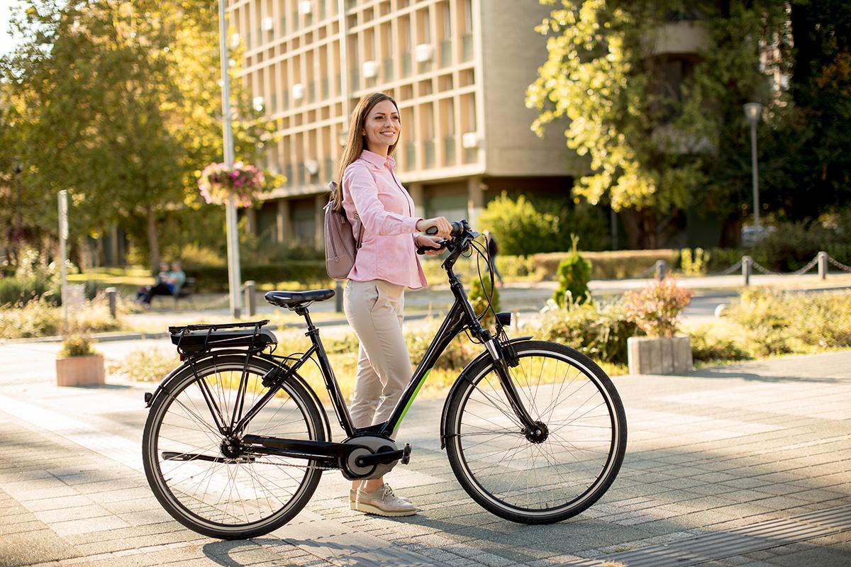 Una donna cammina per la città con la propria città bike elettrica