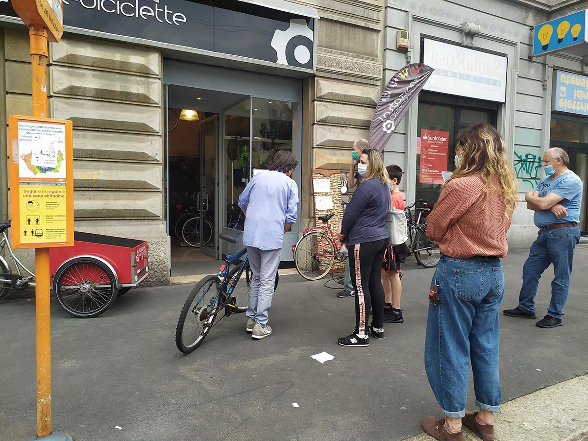 Una folla attende fuori da un negozio di biciclette