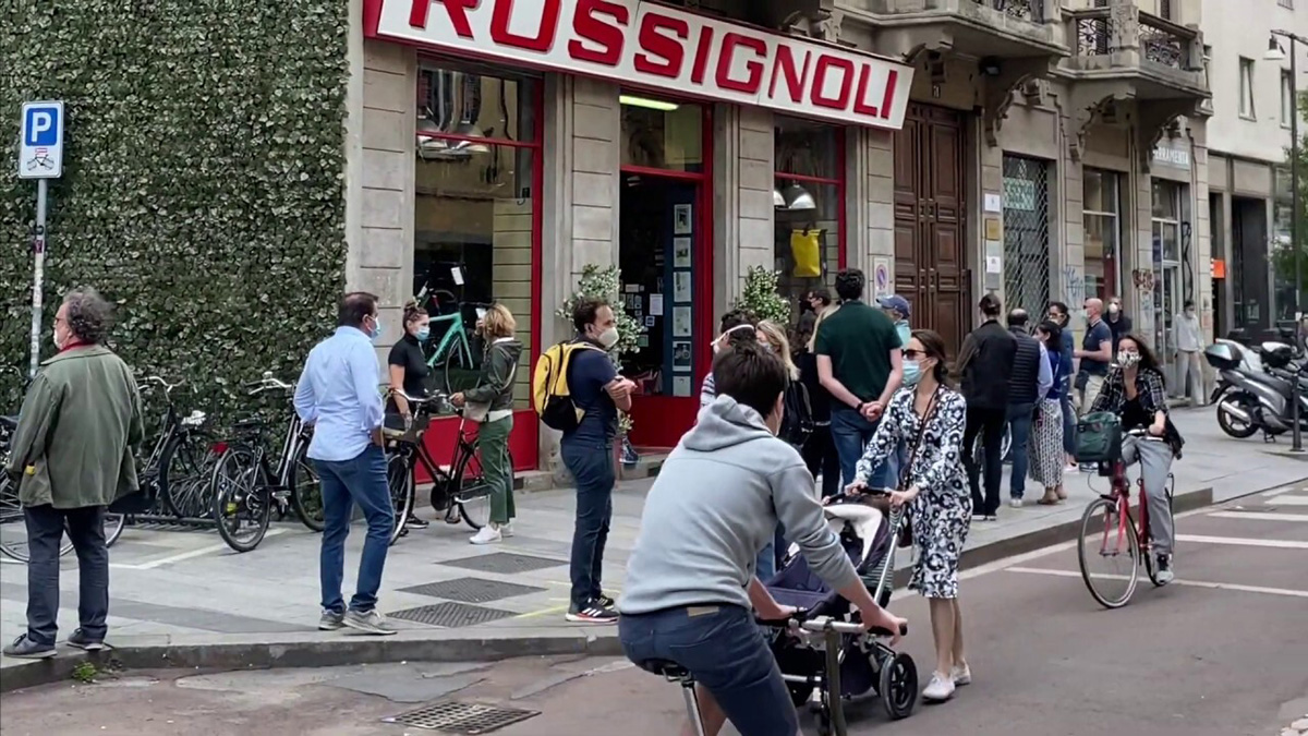 Una folla attende fuori da un negozio di bici