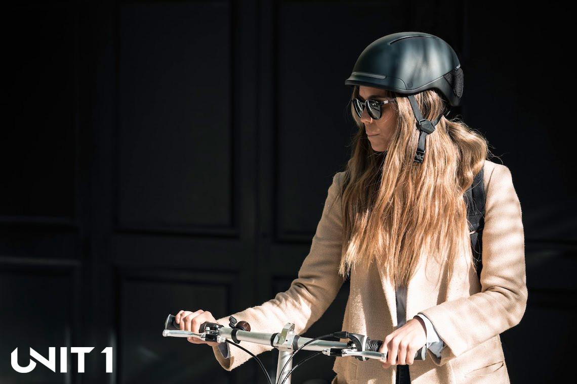 Una ciclista di città esci di casa indossando il casco Faro di Unit 1