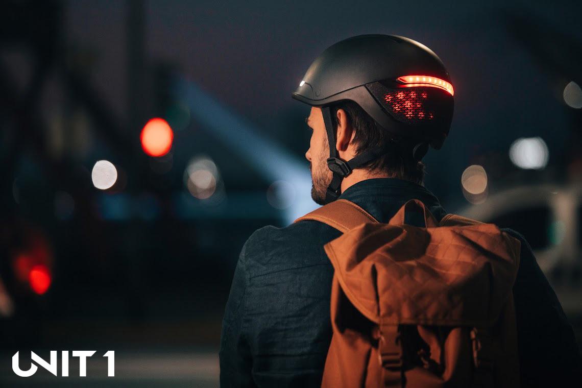 Ciclista di notte indossa un casco Faro di Unit 1 acceso e illuminato