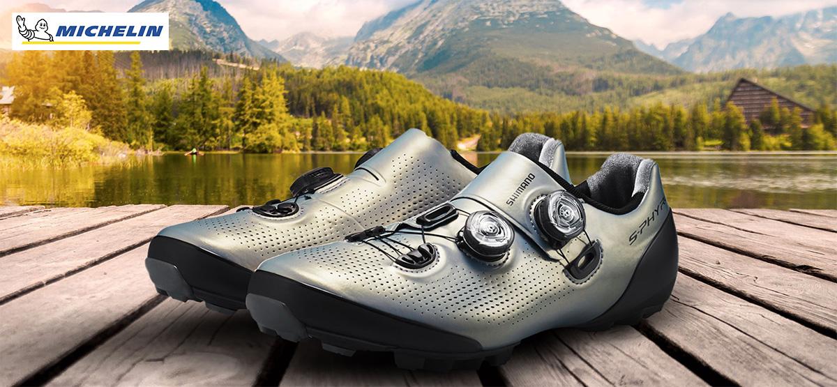 Due scarpe da MTB Shimano in colorazione argento appoggiate su un pontile
