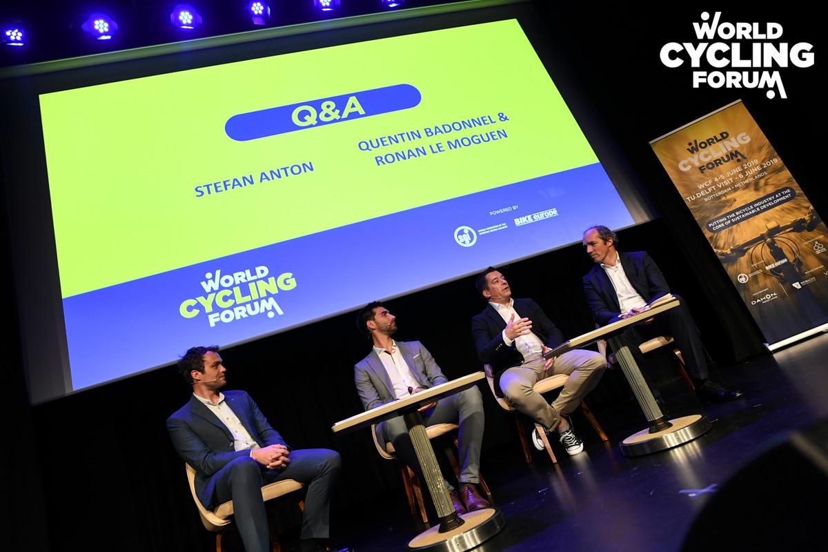 Quattro persone sedute discutono durante una conferenza del World Cycling Forum