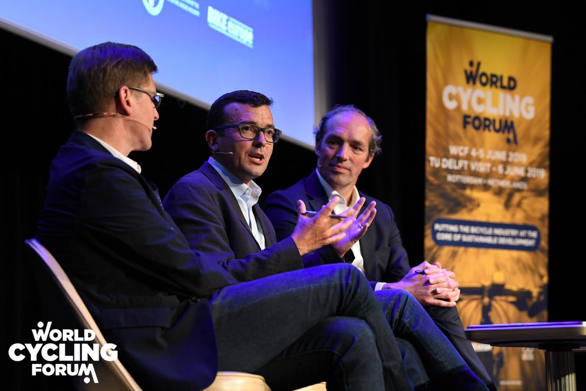 Tre persone discutono tra loro e con il pubblico al World Cycling Forum