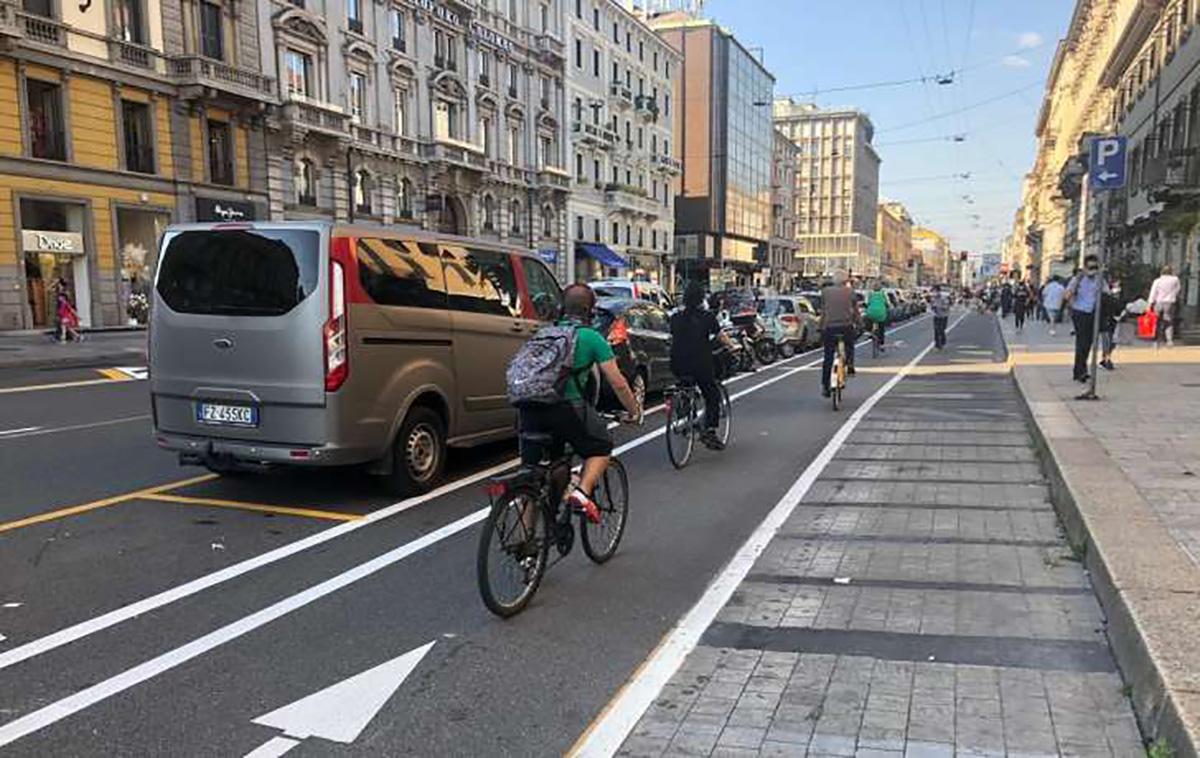 Una fila di ciclisti urbani pedalano sulla ciclabile a fianco della carreggiata