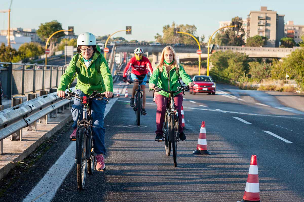 Una famiglia pedala sulla pista ciclabile parallela alla strada