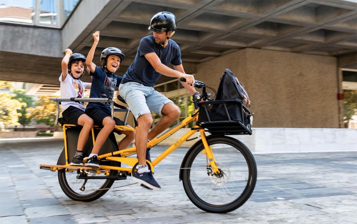 Un uomo trasporta i suoi figli sulla bici cargo