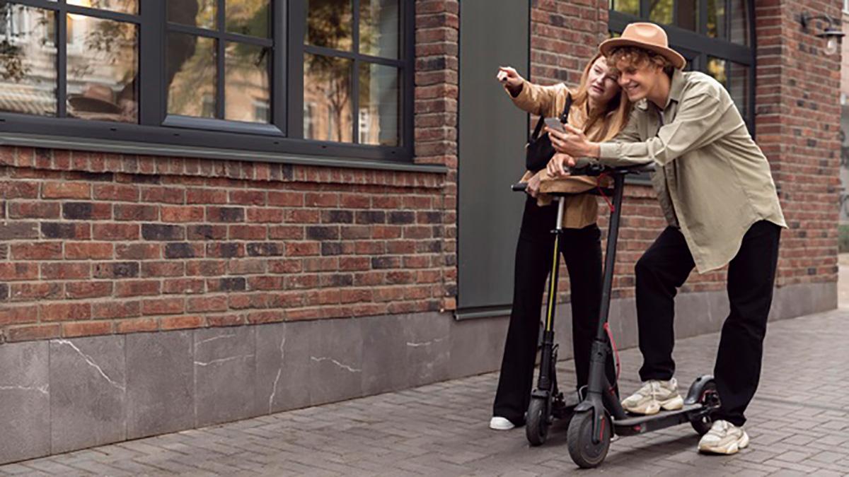 Due ragazzi sui loro monopattini elettrici in città