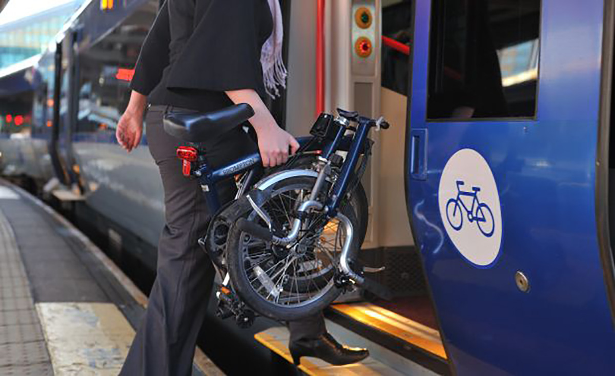 Una donna sale sul treno con la sua bici pieghevole