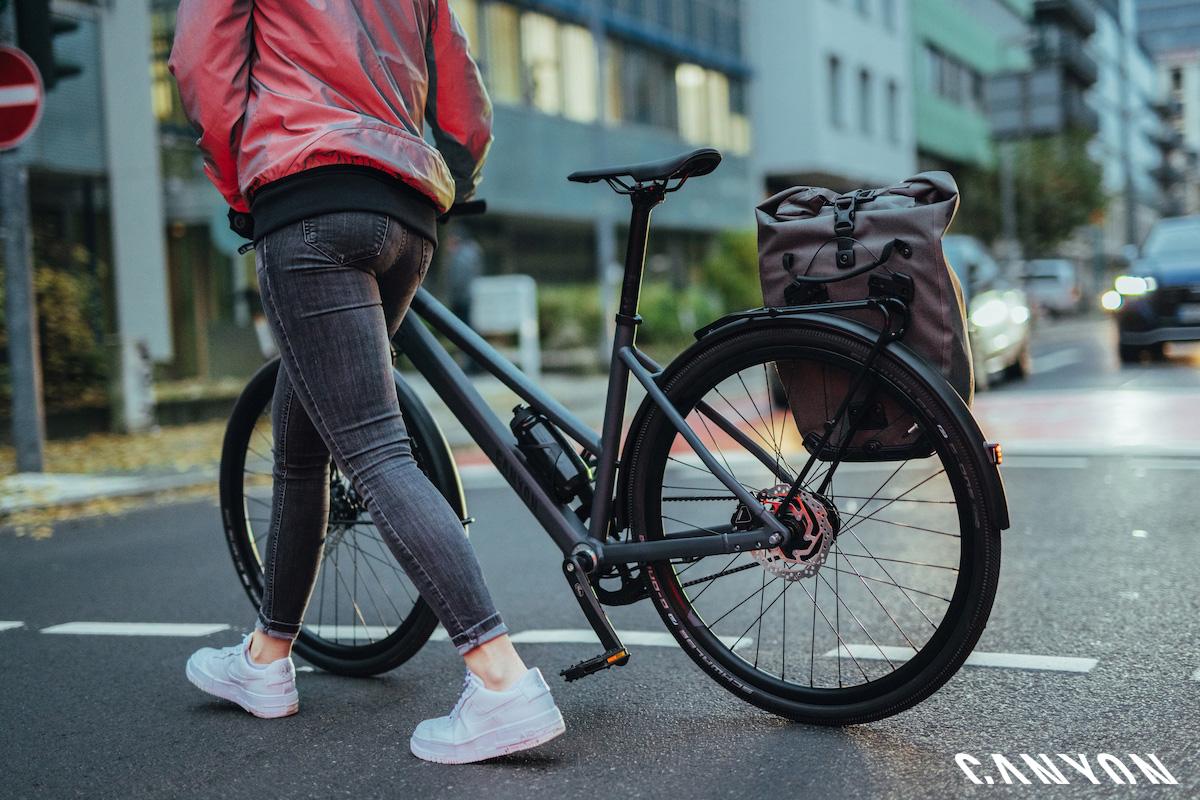 Ciclista donna a passeggio per la città con una bici Canyon Commuter 2021 spinta a mano