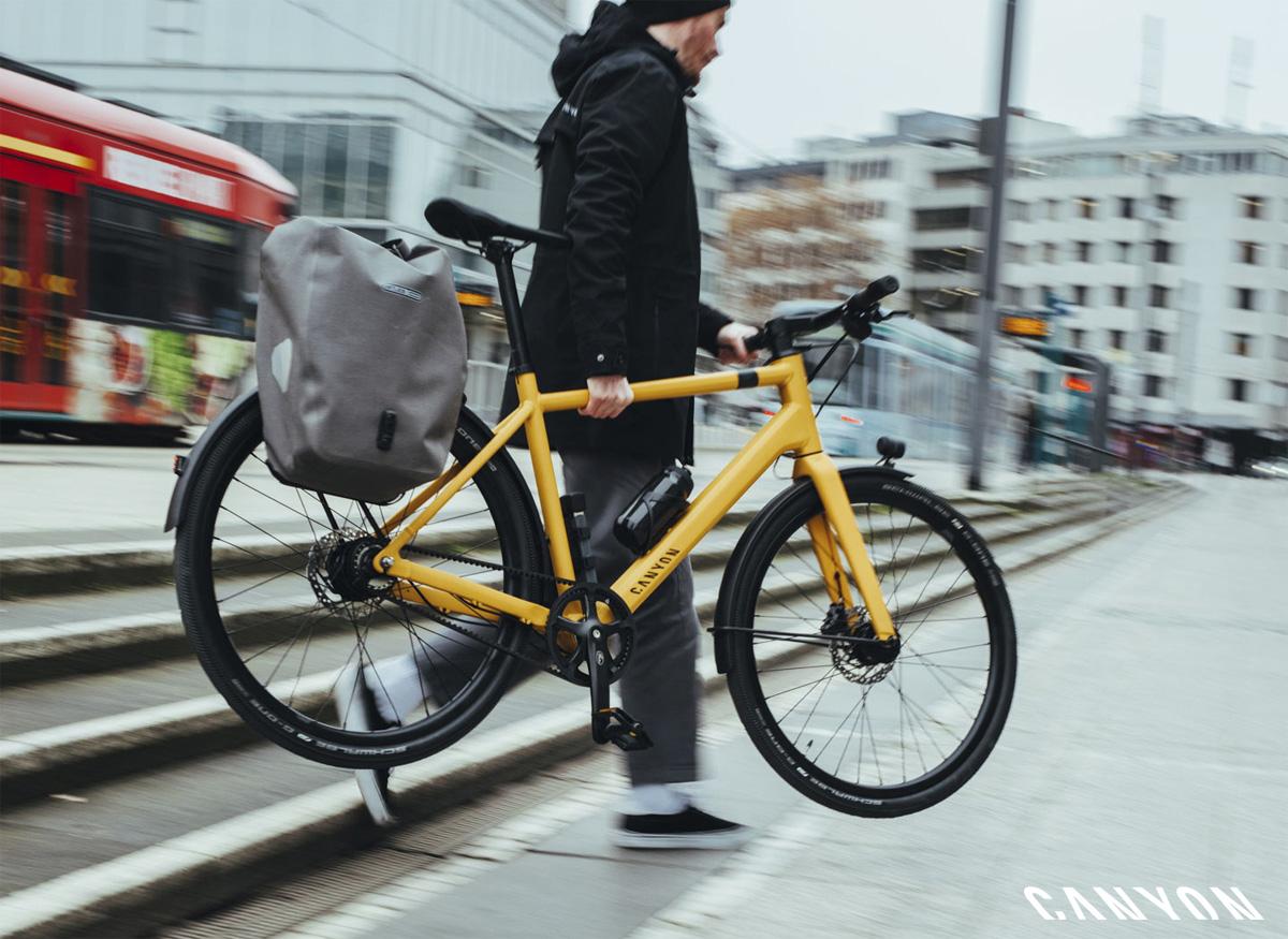 Uomo scende dei gradini portando a mano la bici Canyon Commuter 2021