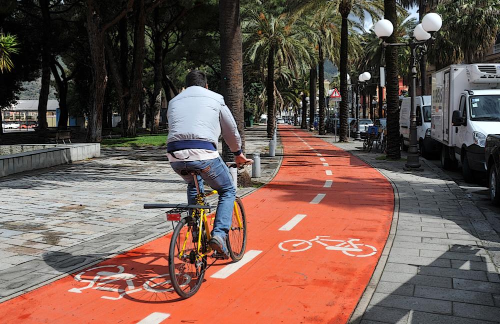 Ciclista urbano si sposta per la città usando una pista ciclabile