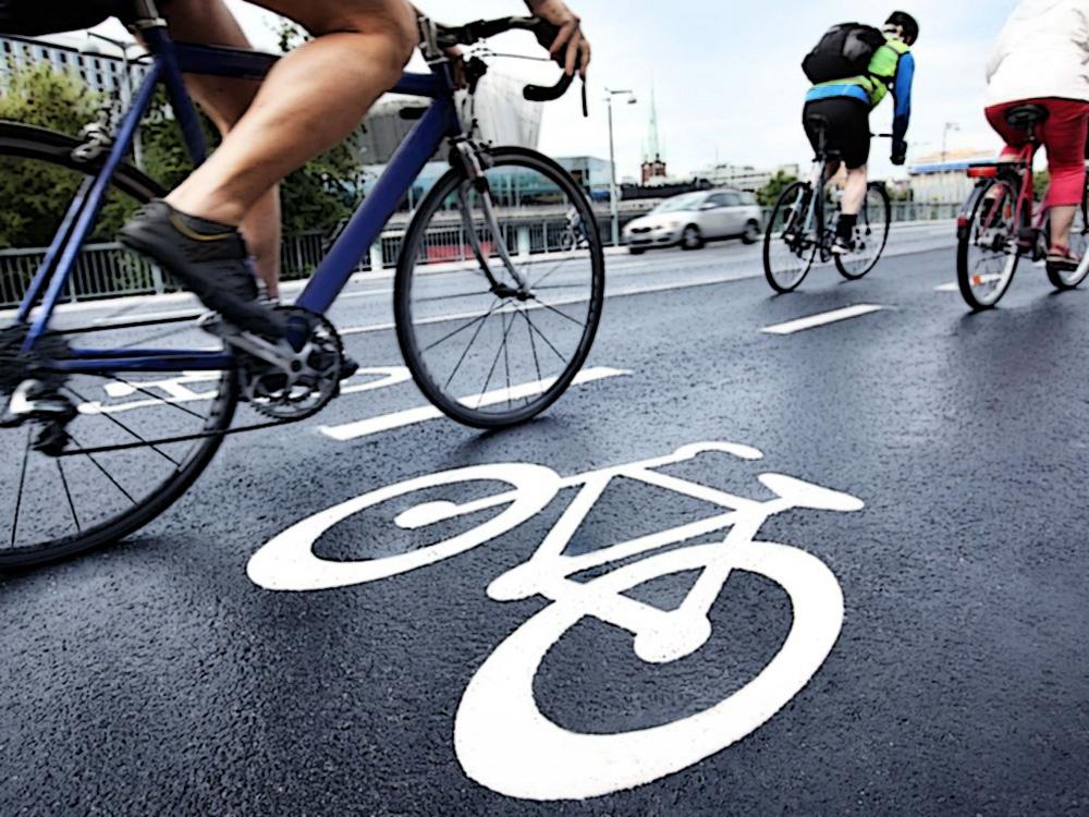 Ciclisti si spostano per la città percorrendo una pista ciclabile