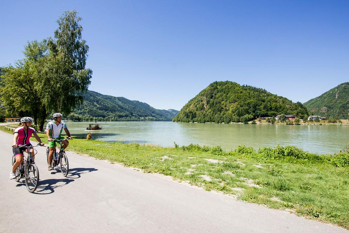Una coppia di ciclisti su una pista ciclabile lungo un fiume