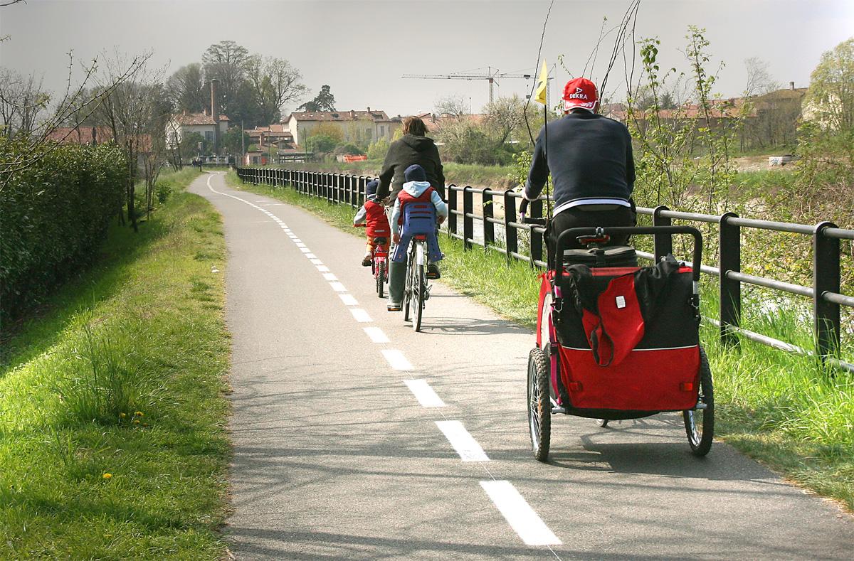 Una famiglia di ciclisti con carrellino percorre una pista ciclabile a fianco di un canale d'acqua