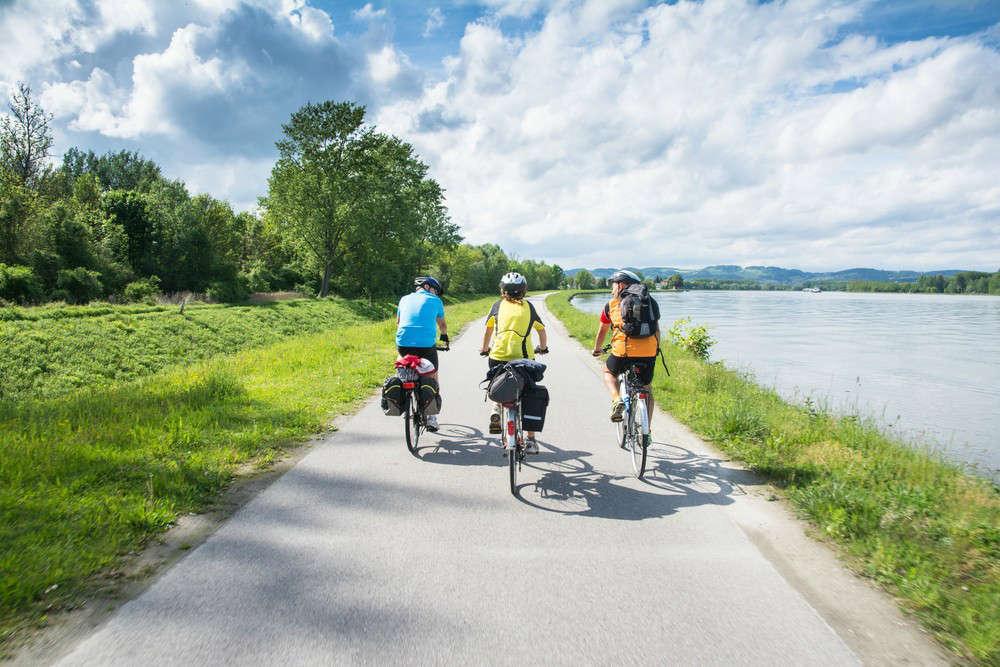 Tre ciclisti percorrono una strada ciclabile a fianco di un fiume