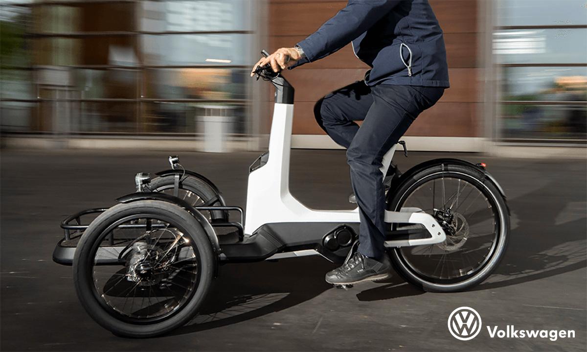 Un uomo pedala in città con la cargo ebike progettata da volkswagen