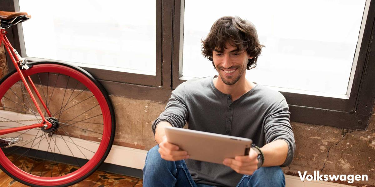 Ragazzo seduto di fianco a una bici cerca informazioni su un tablet