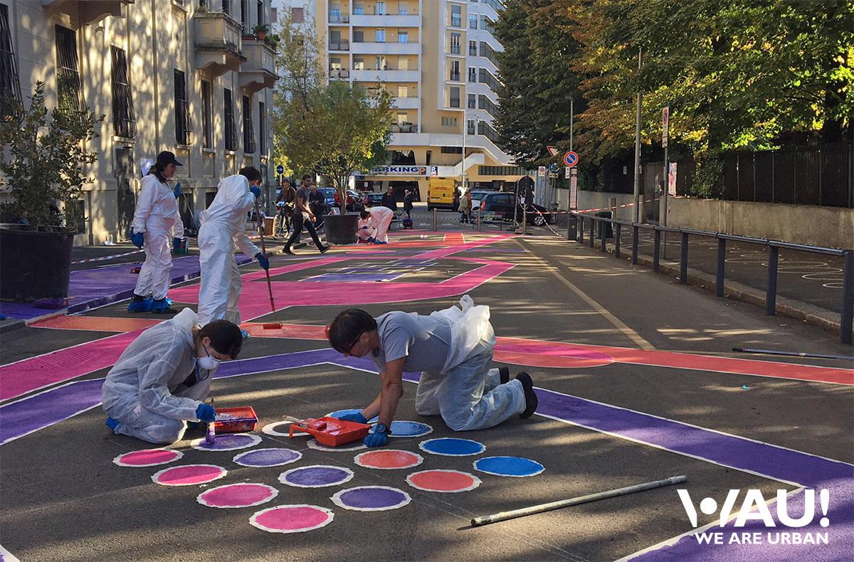 Dei volontari di WAU WeAre Urban dipingono delle decorazioni sulla strada