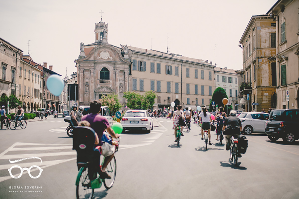 Diverse persone pedalano in sella alla propria bicicletta in una piazza di una città italiana