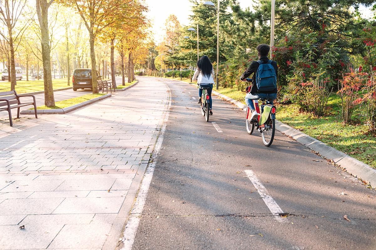 Una coppia di ragazzi pedala in sella a delle ebike sulla strada