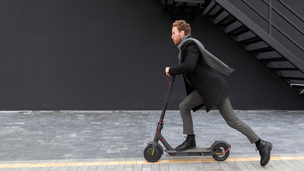 Un uomo ben vestito si muove con il monopattino elettrico per la città