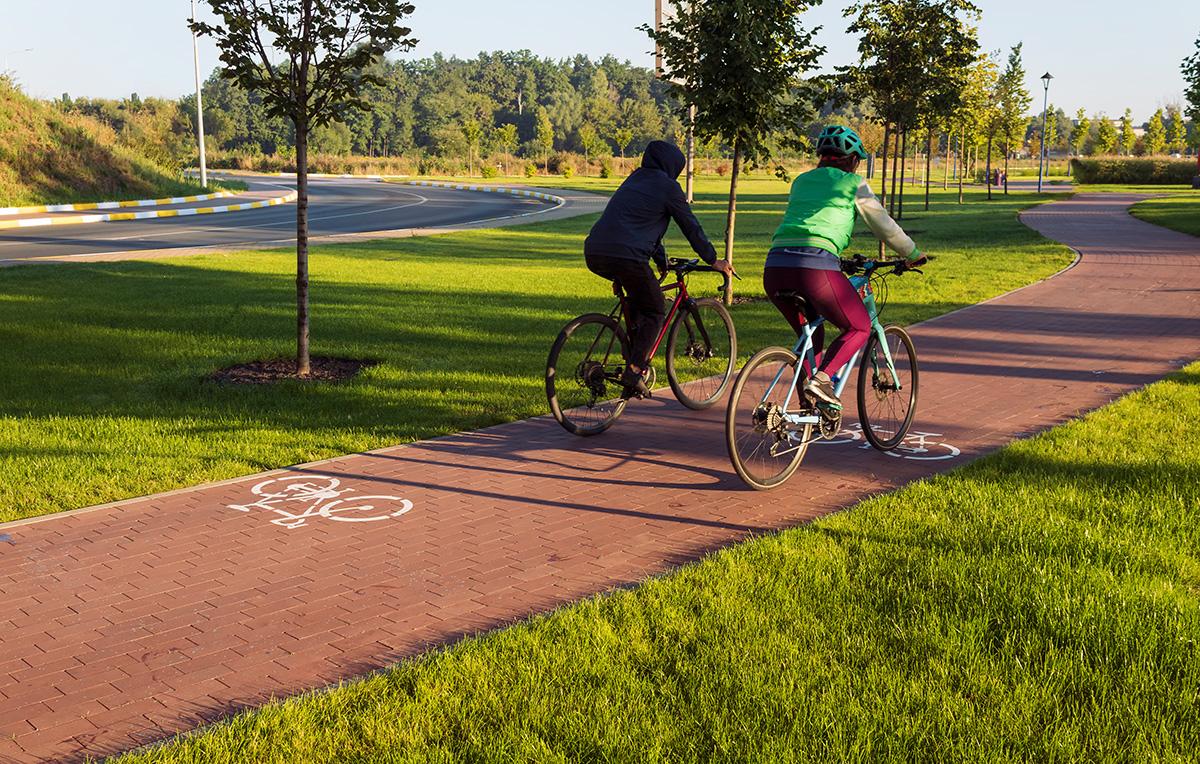 Due donne pedalano sulla pista ciclabile