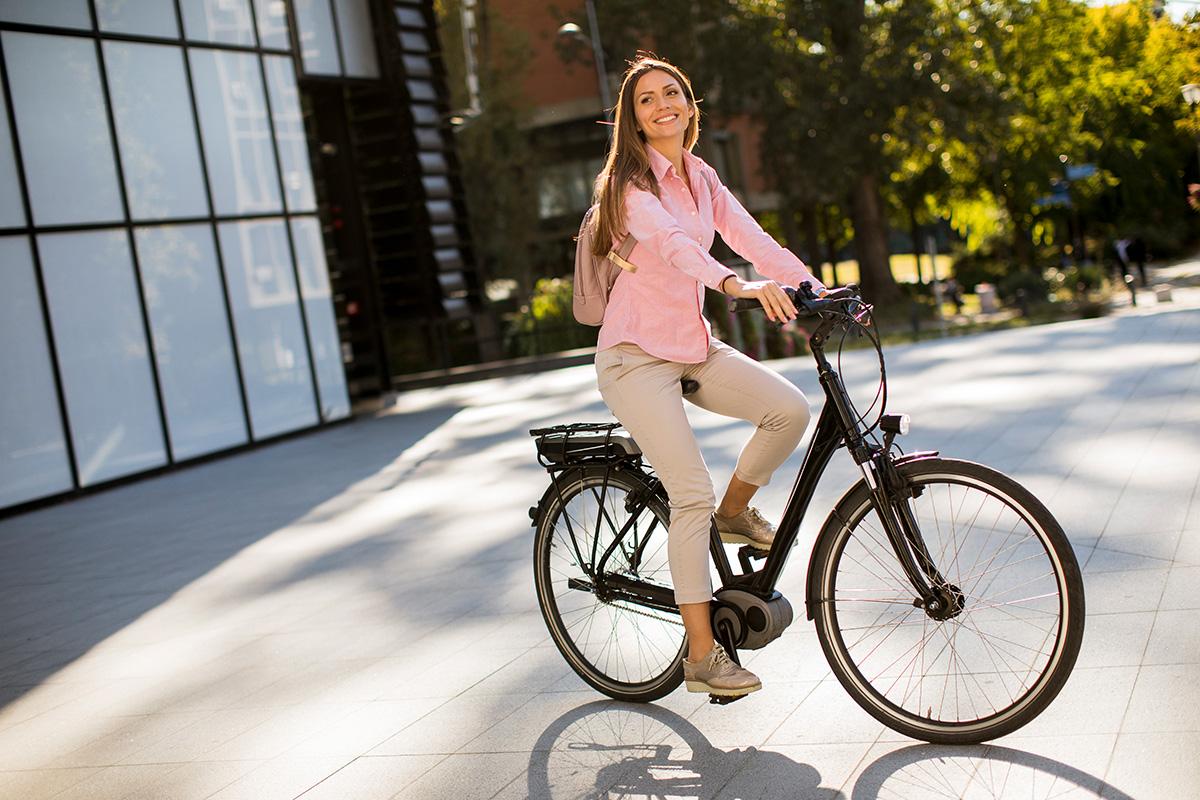 Una ragazza pedala per la città in sella ad una ebike