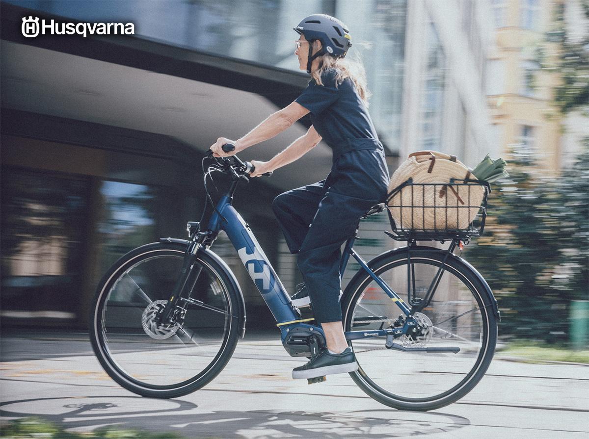 Una ragazza pedala per la città con una ebike urban Husqvarna