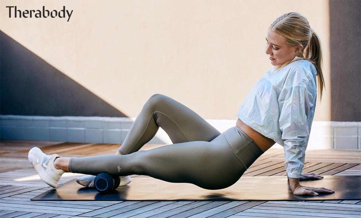 Donna sul tappetino massaggia una gamba col Therabody Wave Duo