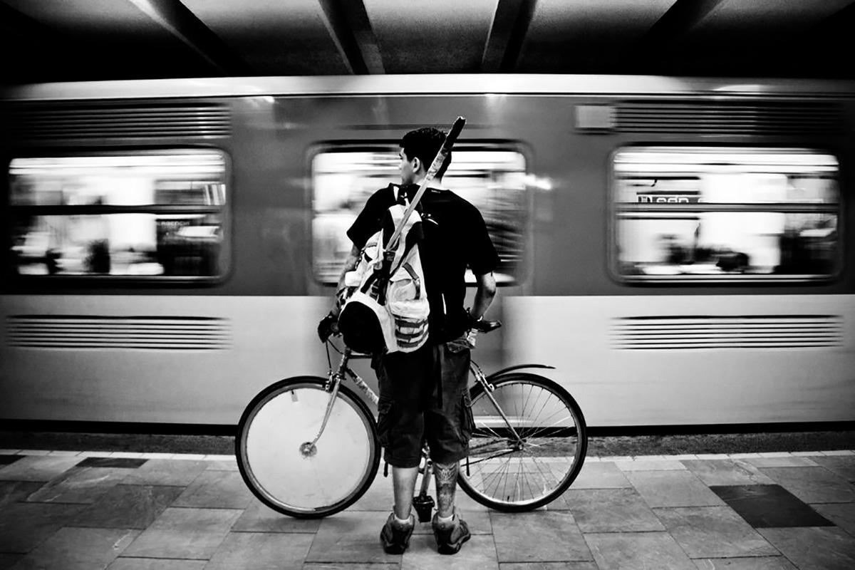 Un ragazzo aspetta di salire sul treno con la propria bici