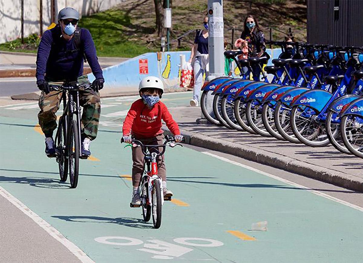 Un bambino pedala su una pista ciclabile seguito dal papà