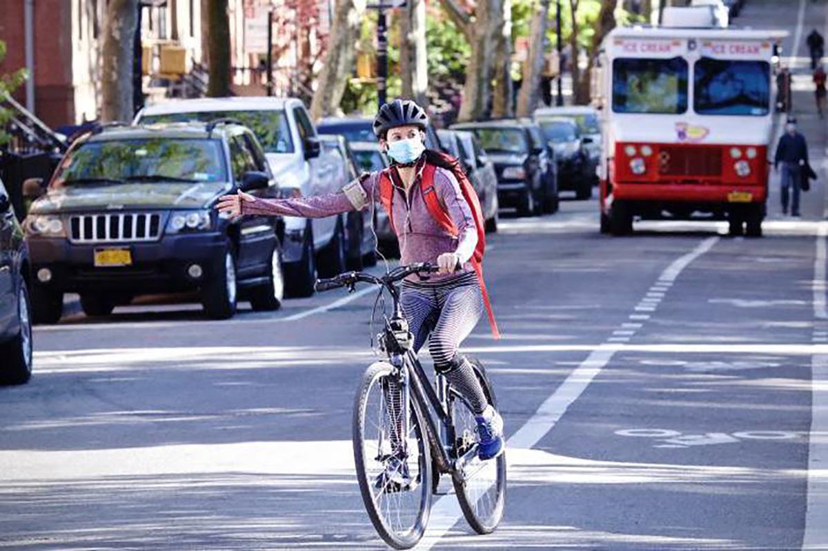 Una ciclista pedala su una strada indicando con il braccio la sua intenzione a svoltare