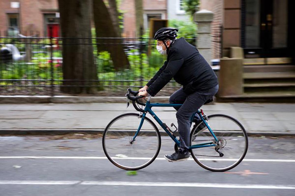 Un ciclista pedala su una pista ciclabile a New York indossando una mascherina