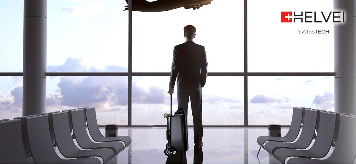 Un signore fermo in aeroporto di fianco al suo monopattino elettrico Helvei Scooter Suitcase & Backpack