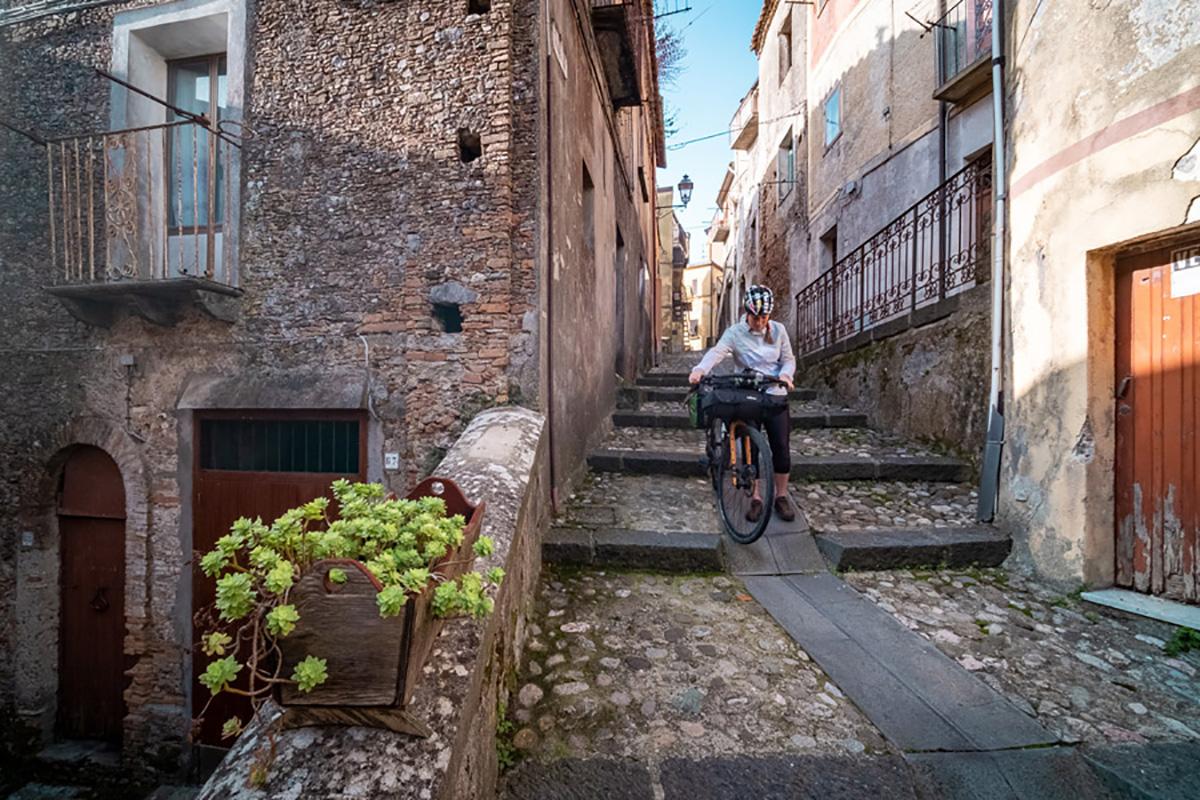 Una ciclista visita un borgo ubicato nella Ciclovia dei Parchi della Calabria