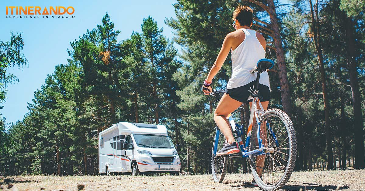 Un cicloturista pedala vicino al suo camper