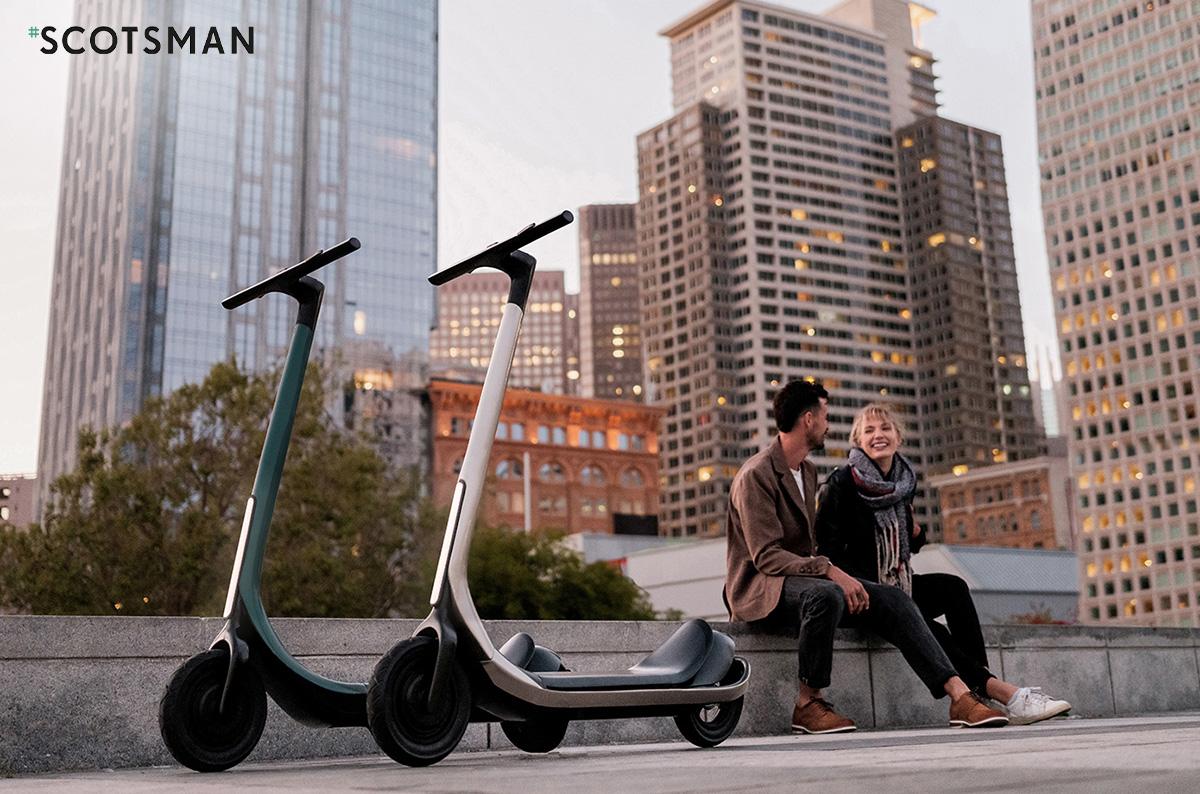 Due ragazzi seduti in città con i loro monopattini elettrici Scotsman 2021
