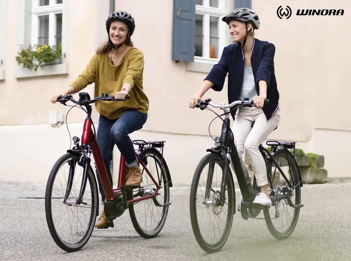 Due donne pedalano in città con le loro ebike Winora 2021