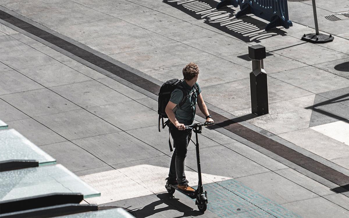 Un uomo viaggia in monopattino elettrica per una strada cittadina